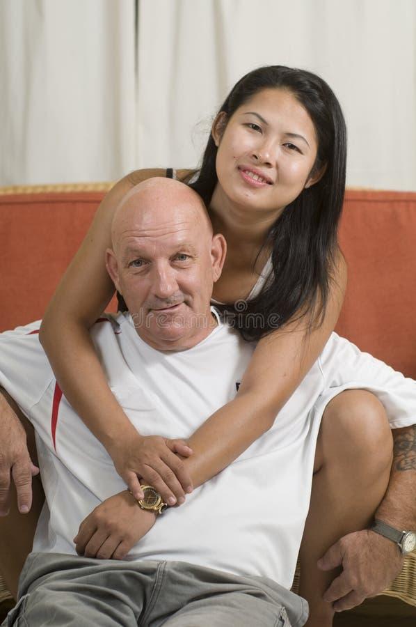 Pares que sentam-se junto e que sorriem imagens de stock royalty free