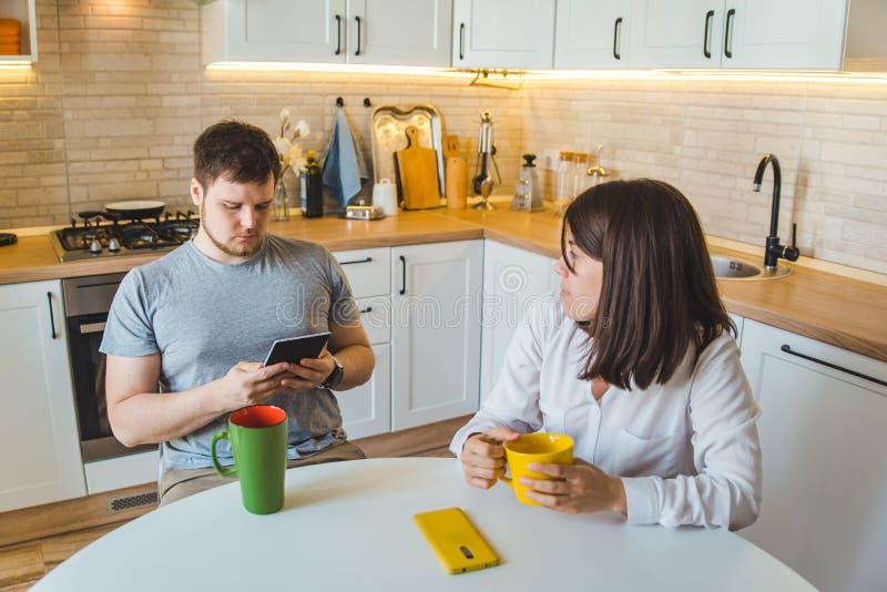 Pares que sentam-se na cozinha na notícia bebendo da leitura do chá da manhã imagens de stock