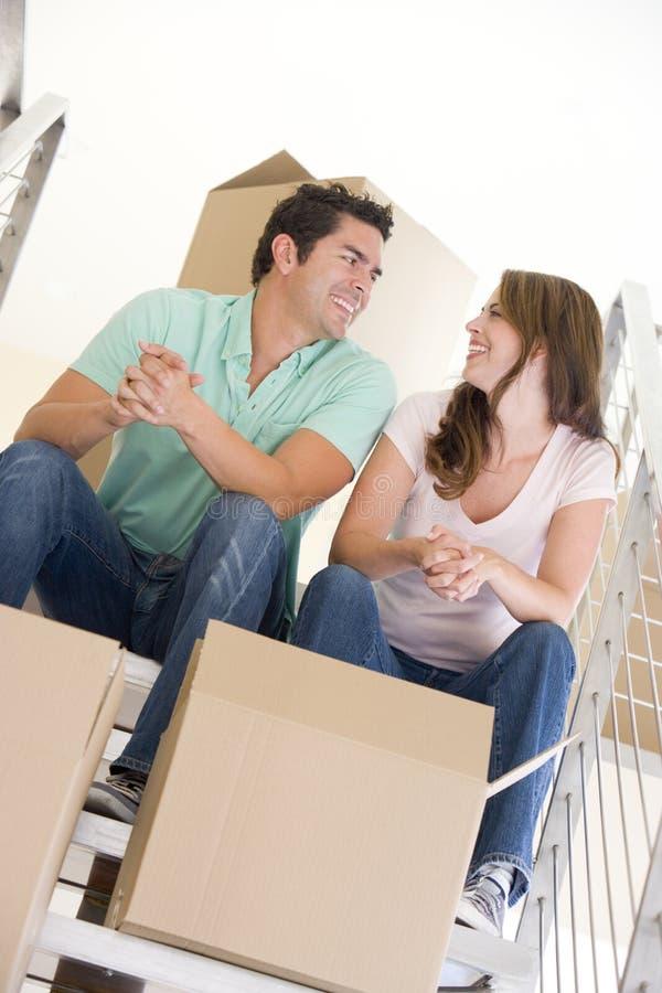 Pares que sentam-se na escadaria com as caixas na HOME nova imagens de stock royalty free