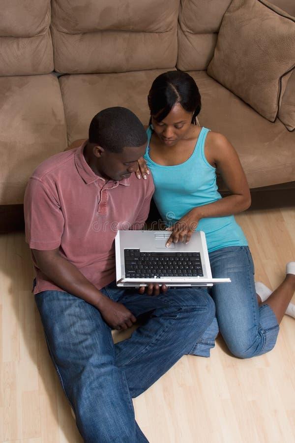 Pares que sentam-se na frente do sofá com COM do portátil fotos de stock royalty free