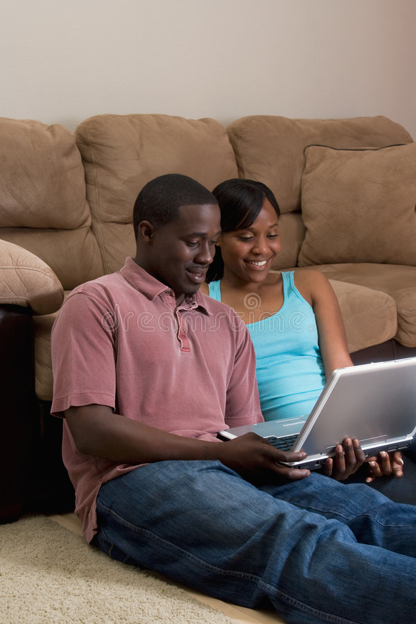 Pares que sentam-se na frente do sofá com COM do portátil foto de stock
