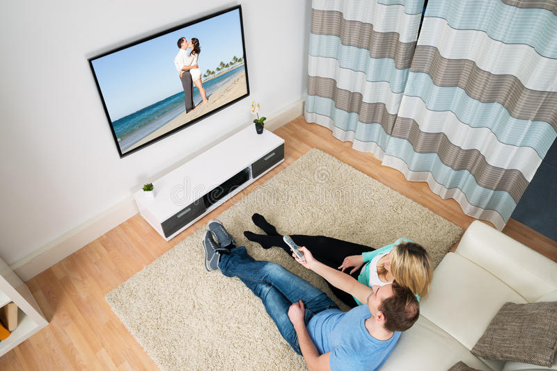 Pares que sentam-se na televisão dianteira fotografia de stock