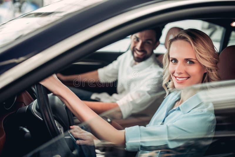 Pares que sentam-se no carro novo foto de stock royalty free