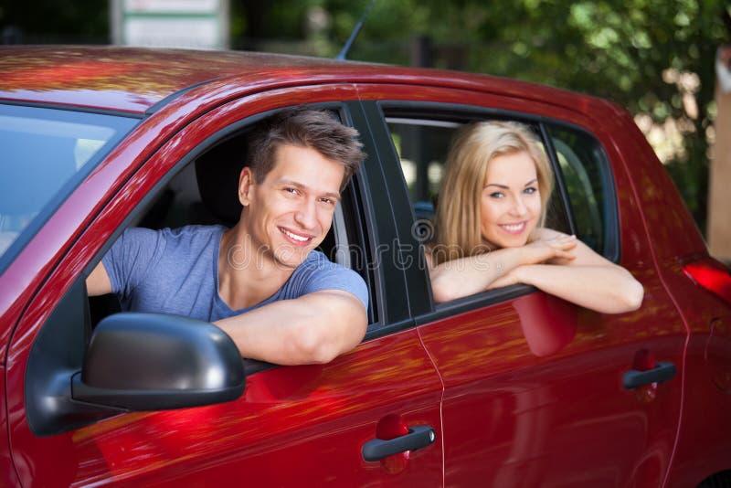 Pares que sentam-se no carro novo imagem de stock royalty free