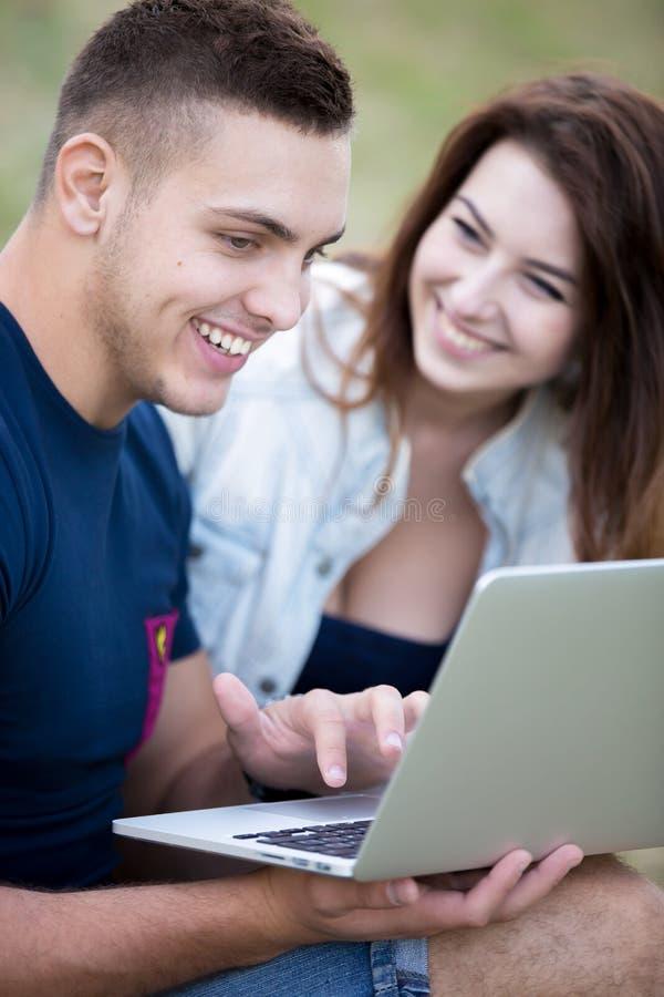 Pares que sentam-se no gramado com portátil foto de stock royalty free