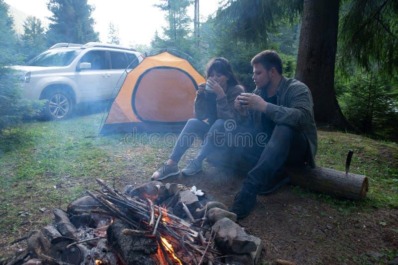 Pares que sentam-se perto do fogo do acampamento e do chá bebendo barraca e suv no fundo imagens de stock