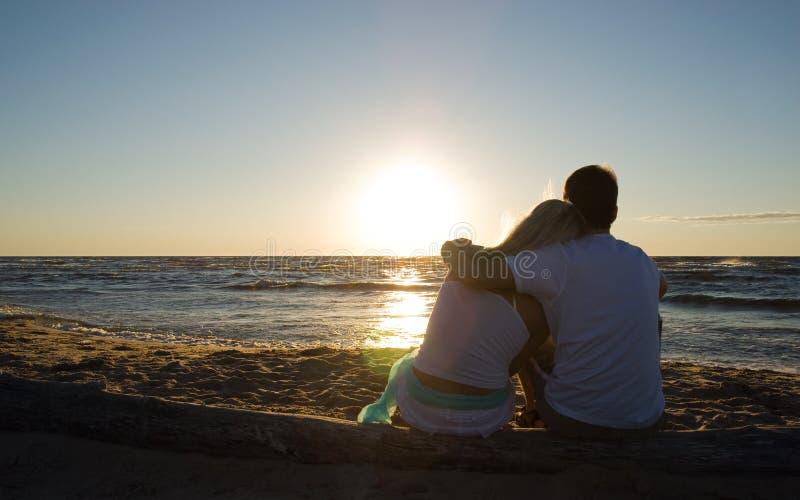 Pares que sentam-se perto do mar no por do sol fotografia de stock royalty free