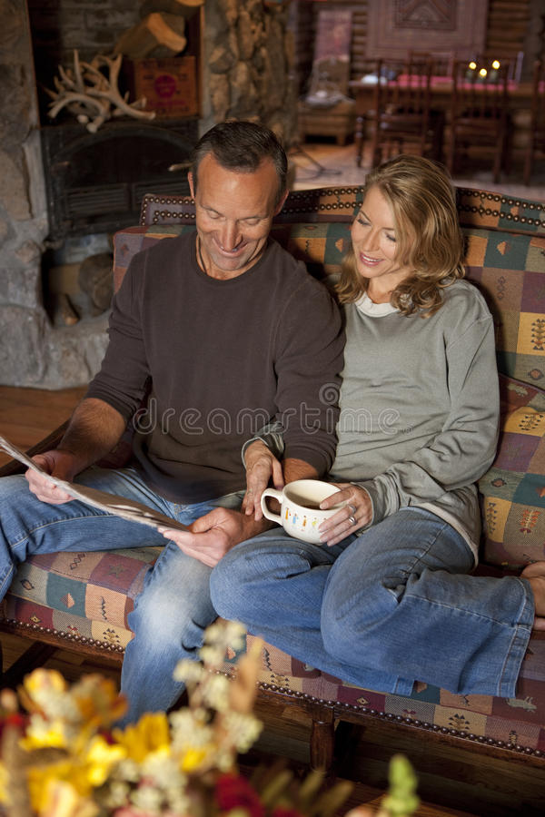 Pares que sorriem e que sentam-se em um sofá imagens de stock