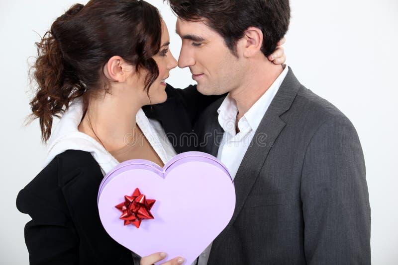 Pares que sostienen la caja en forma de corazón fotografía de archivo libre de regalías