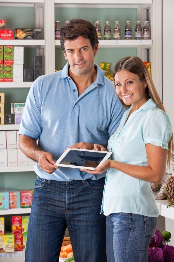 Pares que sostienen la tableta de Digitaces en supermercado foto de archivo libre de regalías