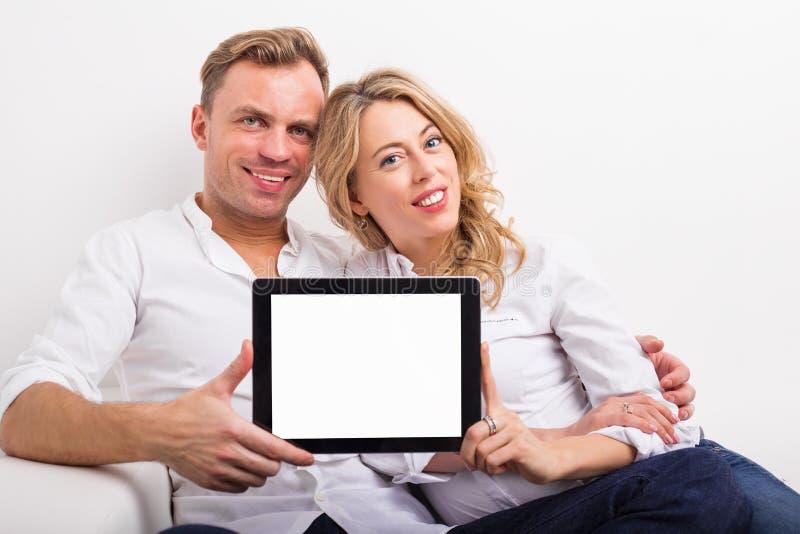 Pares que sostienen la tableta de la pantalla en blanco imágenes de archivo libres de regalías