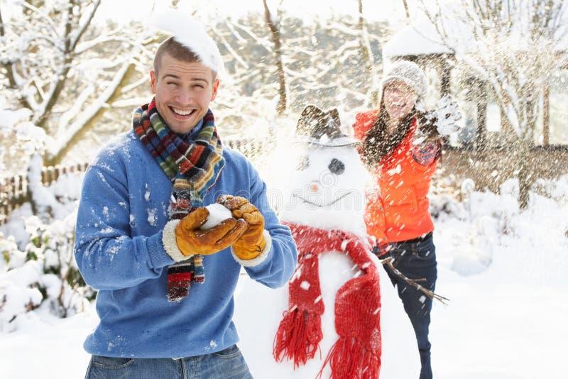 Pares que têm a luta do Snowball no jardim imagens de stock royalty free