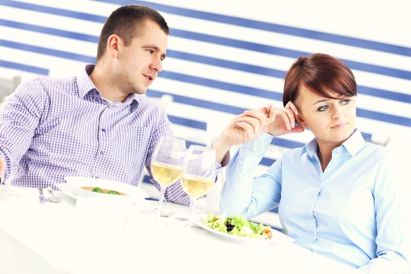 Pares que têm o argumento em um restaurante imagens de stock royalty free