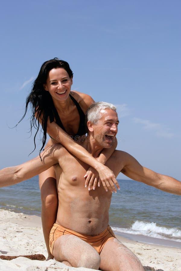 Pares que têm o divertimento na praia imagem de stock royalty free