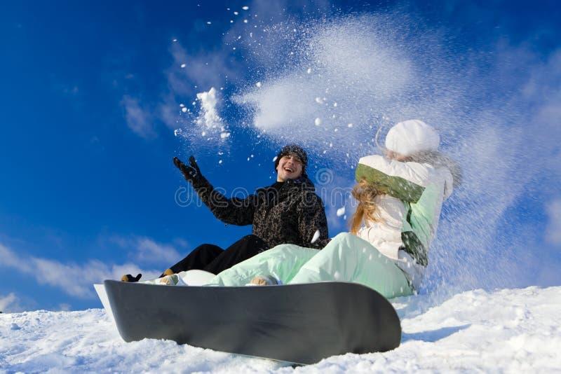 Pares que têm o divertimento no snowboard fotografia de stock