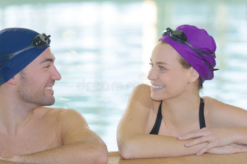 Pares que tienen conversación sobre piscina fotografía de archivo libre de regalías