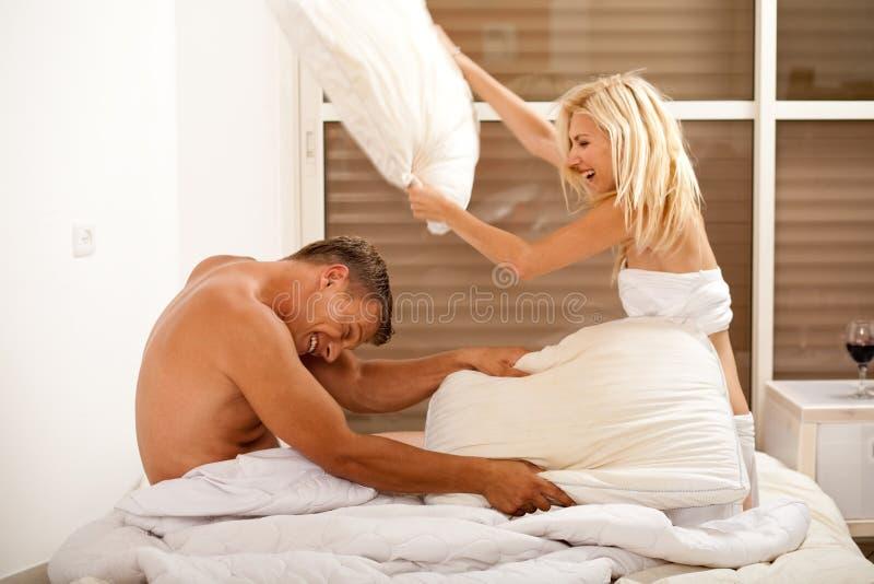 Pares que tienen lucha de almohadilla juguetona en cama imagen de archivo libre de regalías