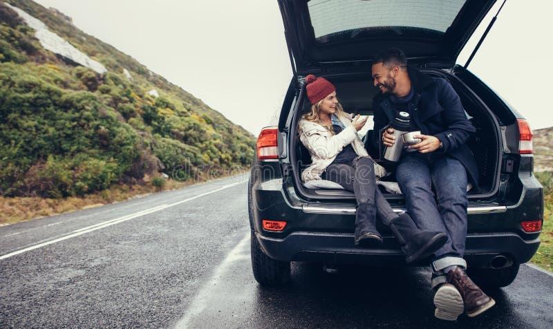 Pares que tienen un descanso para tomar café durante viaje por carretera imagen de archivo libre de regalías