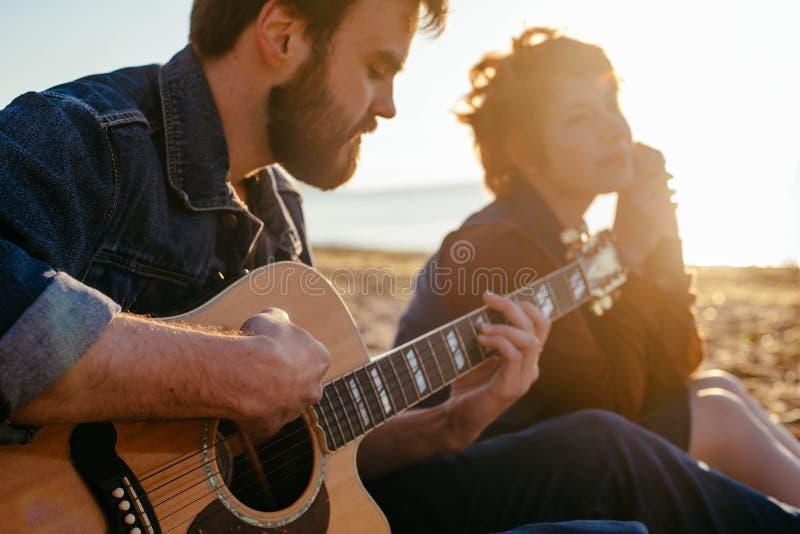 Pares que tocan la guitarra en la playa imagen de archivo libre de regalías