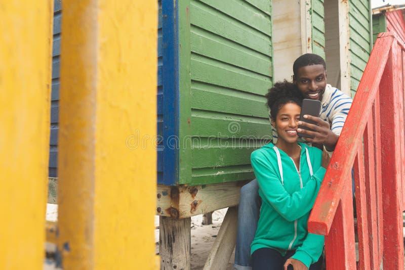 Pares que tomam o selfie ao sentar-se perto da cabana da praia foto de stock
