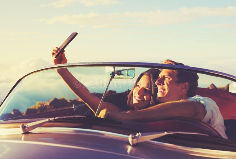 Pares que toman un Selfie en coche en la puesta del sol fotografía de archivo
