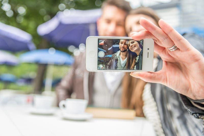 Pares que toman un selfie en una barra imagenes de archivo