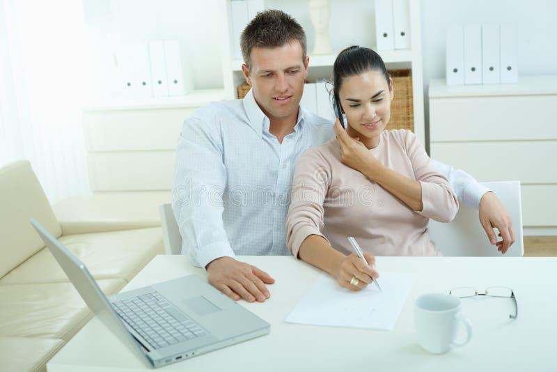 Pares que trabalham em casa imagens de stock royalty free