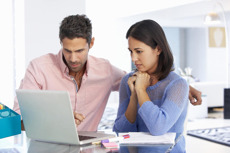 Pares que trabalham no portátil no escritório domiciliário imagens de stock royalty free