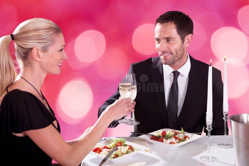 Pares que tuestan las flautas de champán en la tabla del restaurante foto de archivo