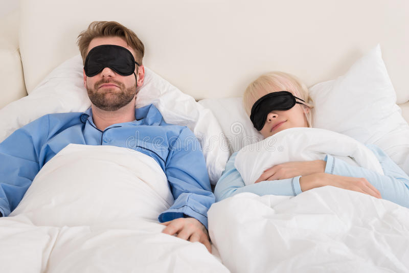 Pares que vestem Eyemask ao dormir na cama imagens de stock royalty free