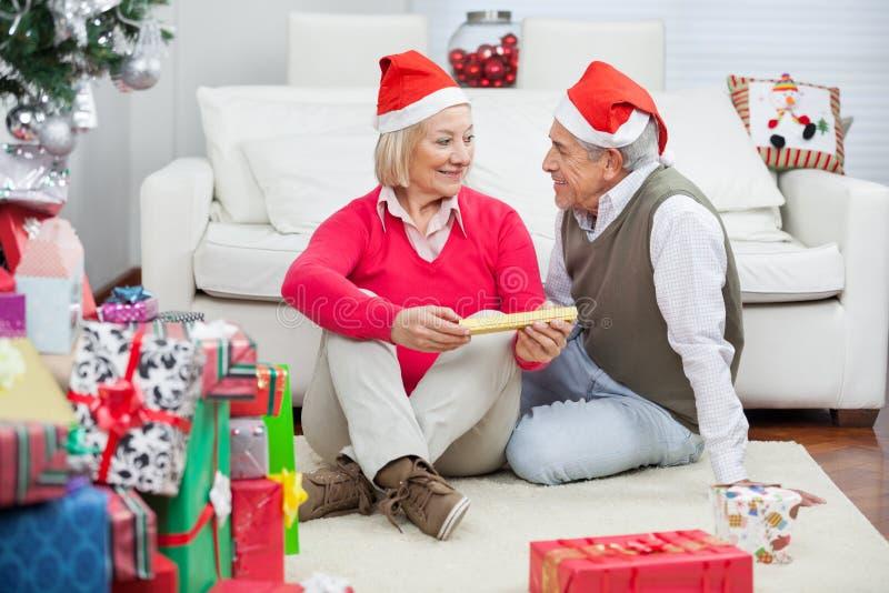 Pares que vestem Santa Hats Looking At Each outro fotos de stock