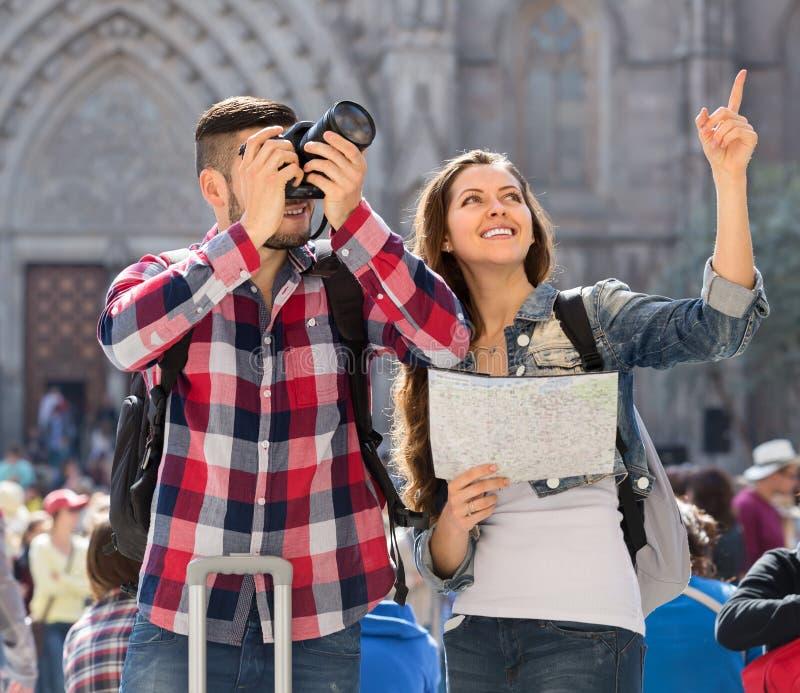 Pares que viajan con el mapa y la cámara imagen de archivo libre de regalías
