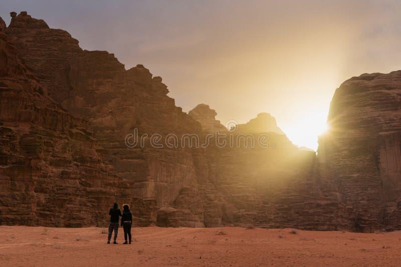 Pares que viajan en el desierto de Wadi Rum en Jordania, disfrutando de salida del sol hermosa por la mañana imágenes de archivo libres de regalías
