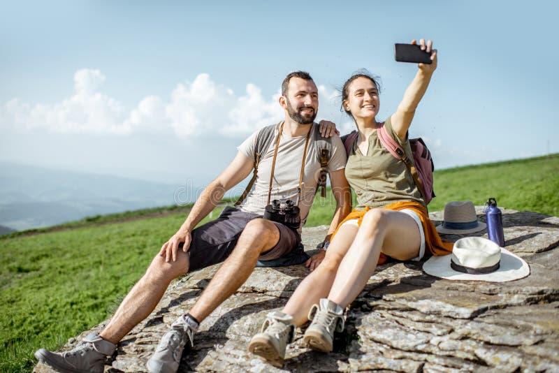 Pares que viajan en las monta?as foto de archivo libre de regalías
