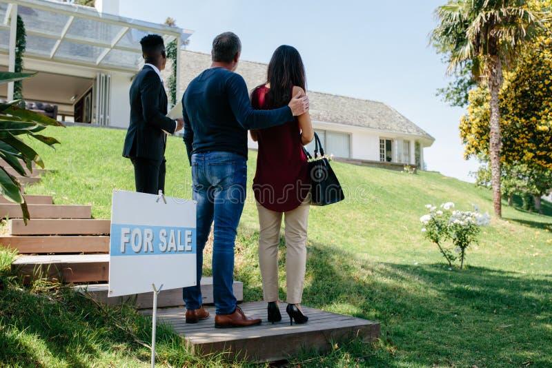 Pares que visitan el chalet de lujo con el agente inmobiliario imagen de archivo libre de regalías