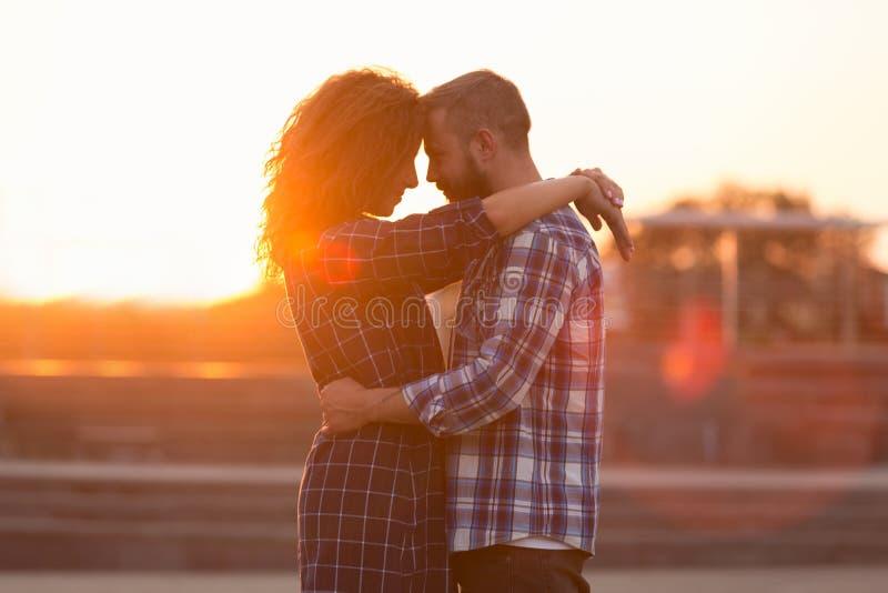 Pares queridos que abrazan y que tocan sus frentes en la puesta del sol fotografía de archivo libre de regalías