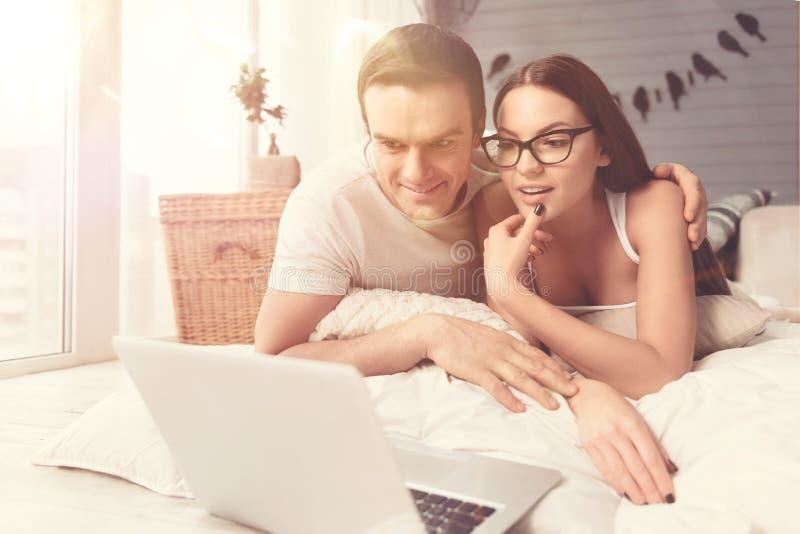 Pares relajados emocionales que miran una película en cama imagen de archivo libre de regalías