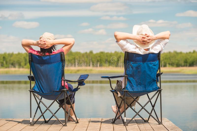 Pares relajados jovenes cerca de una sentada pintoresca del lago fotografía de archivo