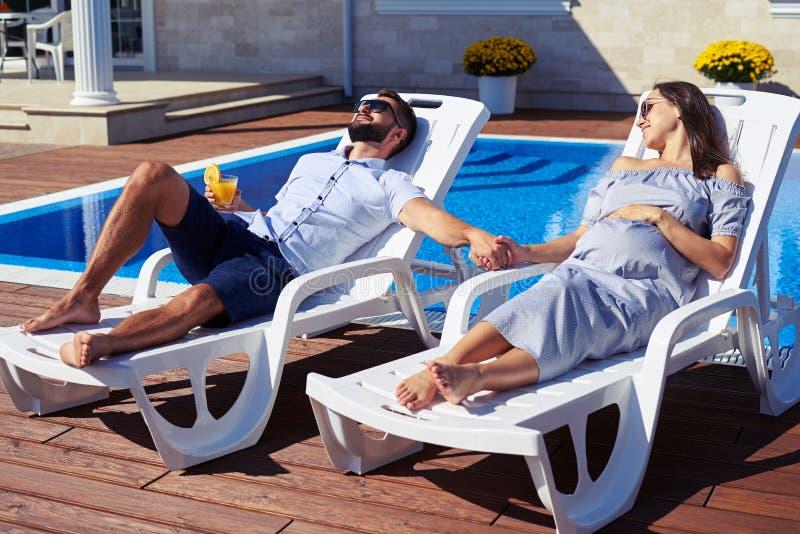 Pares relajados que llevan a cabo las manos cerca de la piscina delante de la casa imagen de archivo