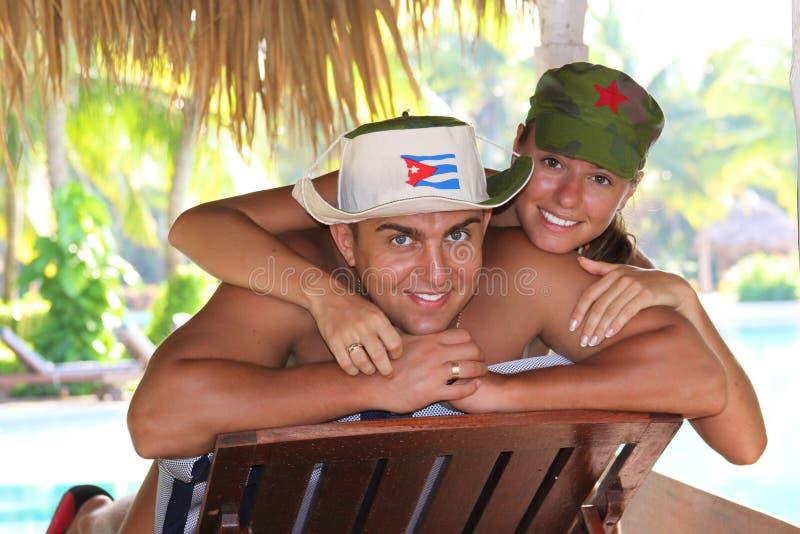 Pares relajados que toman el sol junto en la piscina en verano fotos de archivo libres de regalías