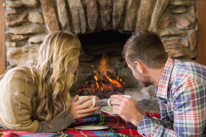 Pares relaxado com os copos de chá que olham a chaminé iluminada fotografia de stock royalty free