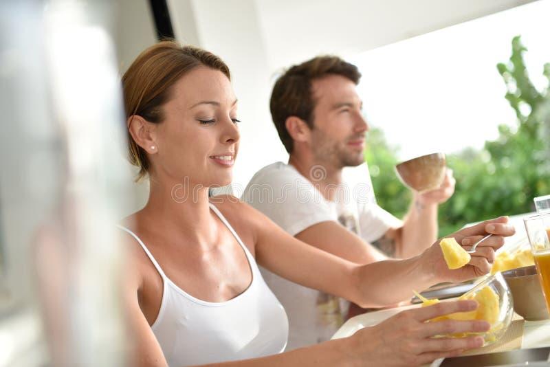 Pares relaxado que comem o café da manhã fotografia de stock royalty free