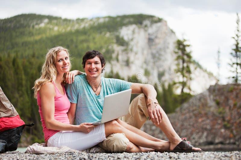 Pares Relaxed con la computadora portátil mientras que acampa fotos de archivo