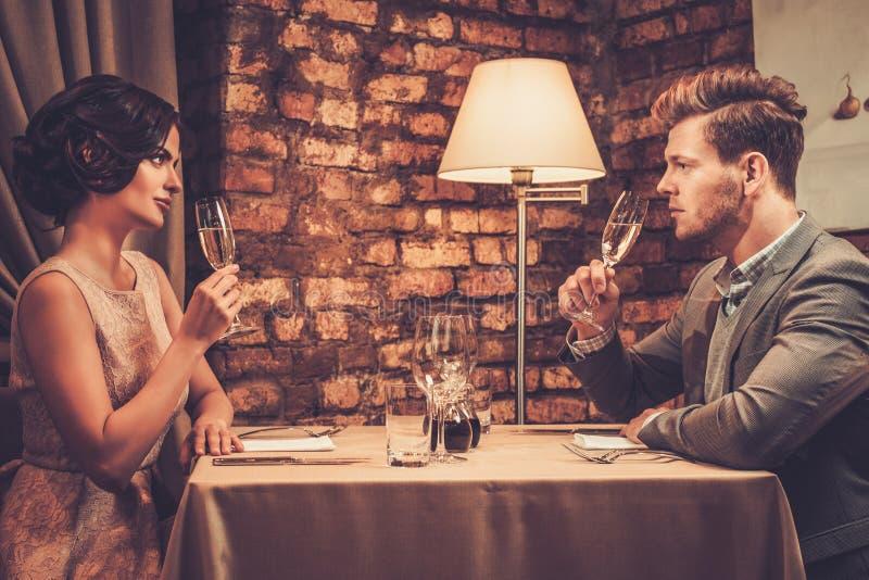 Pares ricos que tuestan con champán en un restaurante foto de archivo libre de regalías