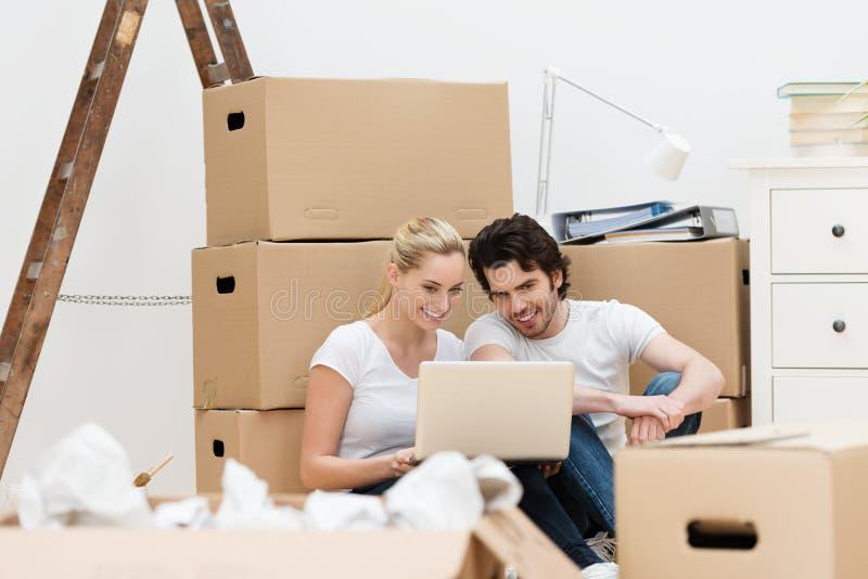 Pares rodeados por las cajas de embalaje usando un ordenador portátil foto de archivo