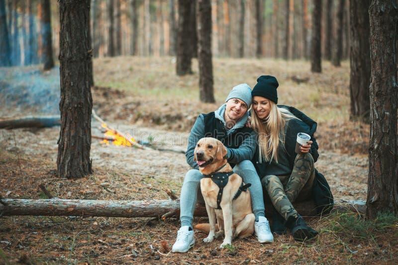 Pares románticos con el perro que se sienta cerca de la hoguera, fondo del bosque del otoño Mujer rubia joven y hombre hermoso foto de archivo libre de regalías