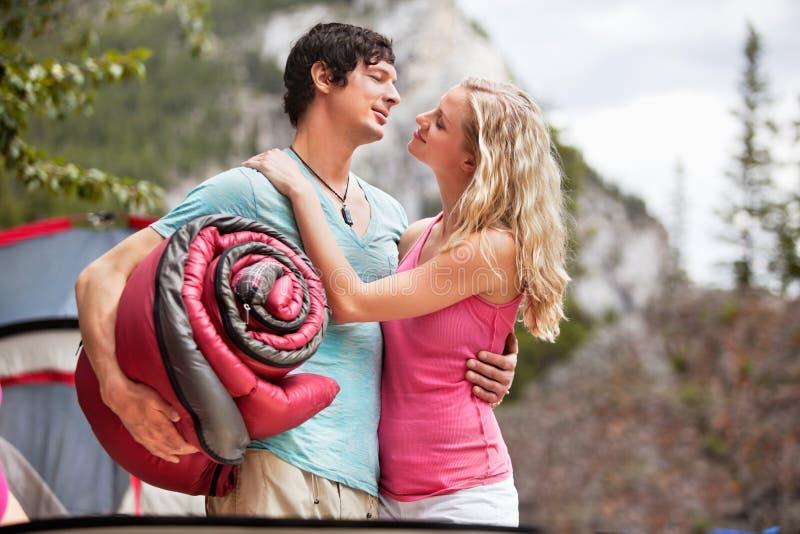Pares románticos con el saco de dormir mientras que acampa imagen de archivo