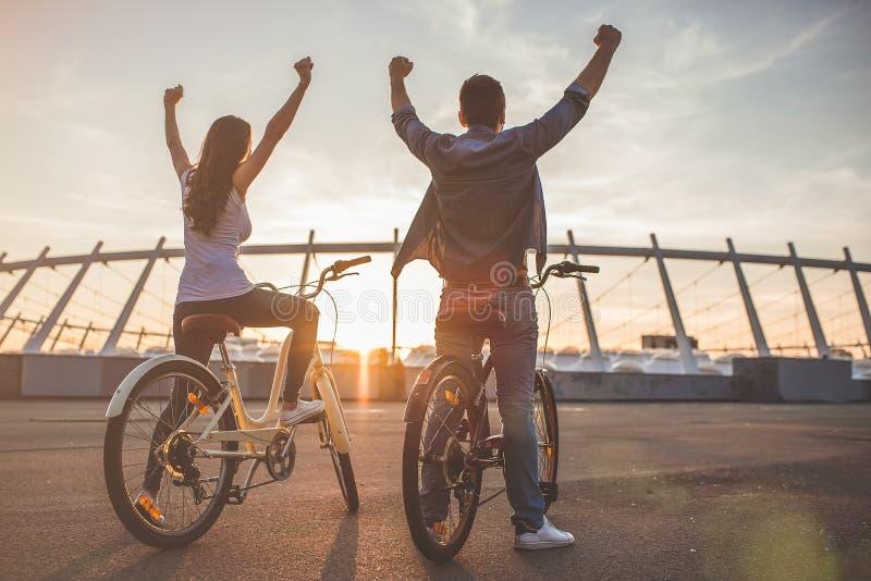 Pares románticos con las bicicletas en la ciudad imagenes de archivo