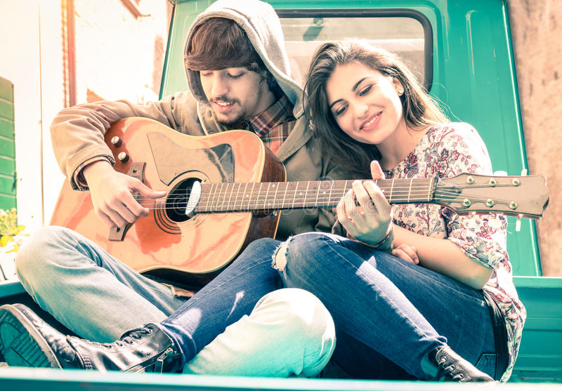 Pares románticos de los amantes que tocan la guitarra en minicar del vintage fotografía de archivo libre de regalías