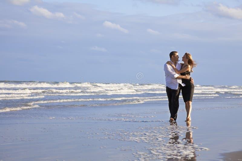 Pares románticos del hombre y de la mujer que recorren en una playa foto de archivo